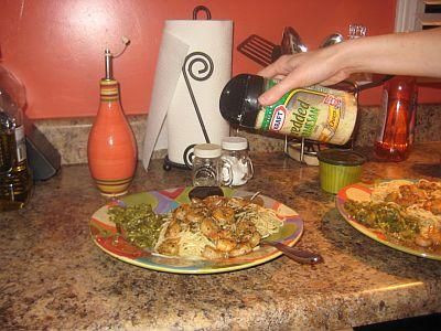 sprinking-the-cheese-on-shrimp-pasta